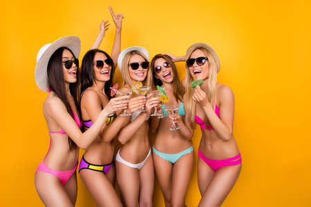 Young five excited ladies are enjoing at the hen party near the swimpool in trendy swim wear and sunglasses, caps, having drinks to celebrate