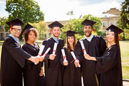 Sechs staunen erfolgreiche attraktive junge Absolventen in schwarzen Roben und Hüten, die ihre Ausbildung abgeschlossen haben, lächeln und verbinden sich mit Diplomen in den Händen, dahinter ist das Collagengebäude, schöner sonniger Tag