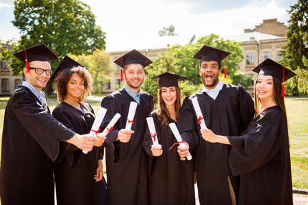 Six amazed successful attractive young graduates in black robes and hats finished their education, are smiling and bonding with diplomas in hands, behind is the collage building, nice sunny day Stockfoto