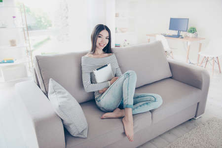 Young charming asian girl  is holding her tablet, sitting on beige couch indoors at home, wearing stripped clothes, jeans, barefoot, relaxing and enjoying