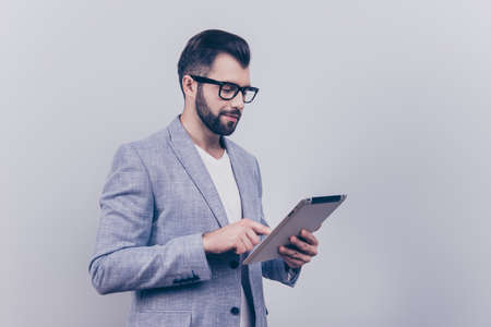 Focused handsome young brunet bearded stock-market broker is typing on his tablet, standing in a formal wear on the pure background. So serious and intelligent, successful and stylish