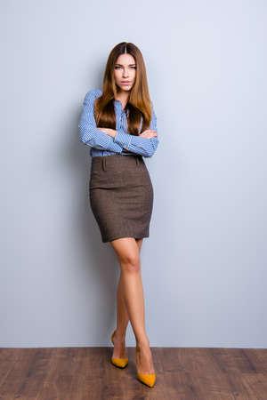 우아한 비즈니스 레이디 변호사의 교차하는 손 및 다리와 꼬리 치는 포즈에서 서의 전체 크기 사진. 그녀는 너무 섹시하고 유혹적으로 보입니다.