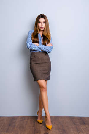 Full size photo of elegant business lady lawyer standing in flirty pose with crossed hands and legs. She looks so sexy and tempting Foto de archivo