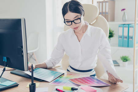decorating: Creative occupation, making decision. Close up of asian female architect, choosing the colors for new project, looking at the pantone, in formal wear, glasses Stock Photo