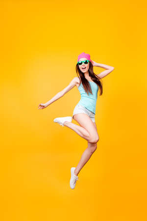 Girlish, funky, happiness, dream, fun, joy, summer concept. Very excited happy cute asian teen is jumping up, in summer outfit, sun glasses, hat, on bright yellow background Stockfoto
