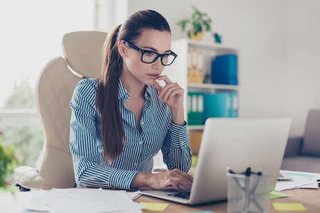 El economista serio joven pensativo de la señora del asunto está pensando qué decisión a hacer en su lugar de trabajo ligero moderno en la oficina, llevando el equipo terminante y los vidrios