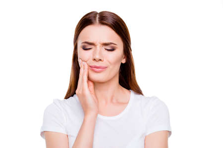 Dental health concept. Portrait of sad brown-haired young woman, having strong toothache, isolated on white background, in white casual outfit
