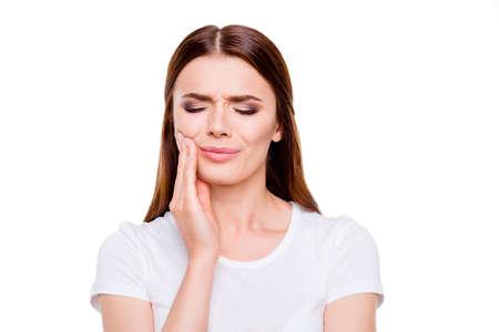 Tandheelkundige gezondheid concept. Portret van triest bruinharige jonge vrouw, met sterke kiespijn, geïsoleerd op een witte achtergrond, in witte casual outfit