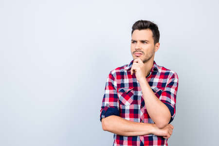 Young guy in checkered casual wear is looking sceptical, has a grimace of distrust on light blue background Stock Photo