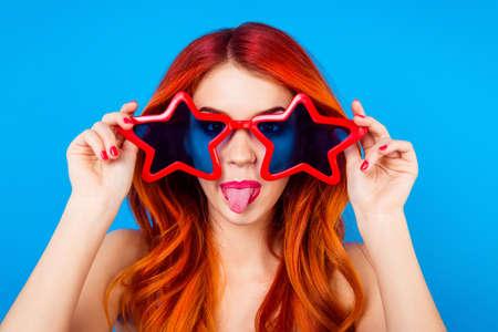 Jonge vrolijke foxy met grote grappige sterglazen en uit tong voor de gek houdt rond op de blauwe achtergrond