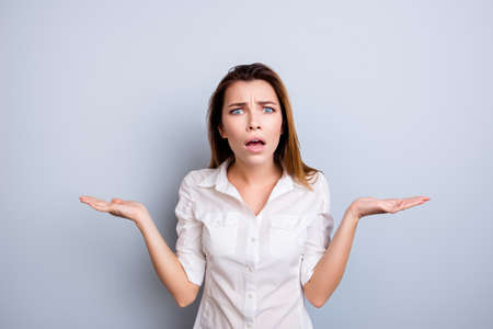 choise: Really?! Shocked and frustrated young lady in formal wear is surprised, standing isolated on the light background, holding copy space