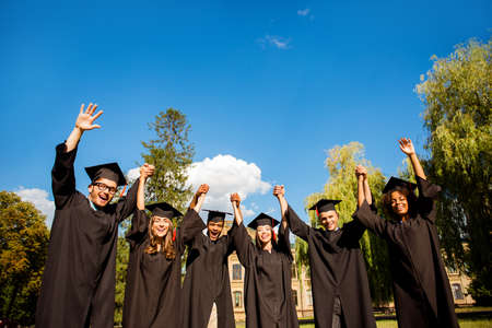 Six excited successful graduates in black robes and mortar-boards with red tassels are holding and rising their hands together. They did it, passed exams, finished course of studies, got the degree