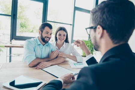 Glückliches junges Paar umfaßt, einen Schlüssel von ihrer zukünftigen Wohnung von einem Vermittler erhalten und Vertrag unterzeichnend, sind alle in den formalen Ausstattungen, nettes helles Bürodesign gekleidet