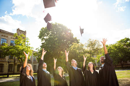 Six successful international young graduates in black robes and hats finished their education, throw mortar boards in the sky, university building behind, nice sunny summer  day Stock Photo