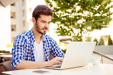 Stylish freelancer is working on his computer, sitting outdoors on a summer day, with cup of coffee, nice city view and green tree behind him