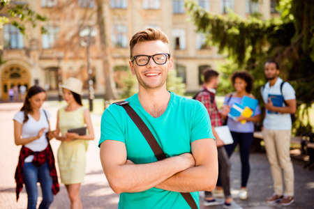 Close up focused photo of young successful blond nerdy student, standing with crossed arms and smiles, behind are his classmates, park near college, sunny day, carefree and enjoyable mood Stock Photo
