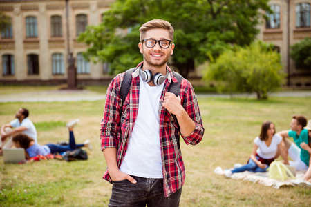Young successful blond nerdy student is standing with backpack and headphones, smiles, behind are his classmates, park near campus, sunny day, carefree and enjoyable mood Stock Photo