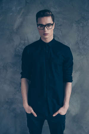 Vertical photo of thoughtful young stylish guy in trendy clothes and spectacles holding his hands in pockets Stock fotó