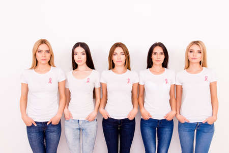 Cancer, medicine, women health concept - cropped photo of five young ladies in white tshirts with pink breast cancer awareness ribbons on breast and jeans, standing on pure white background