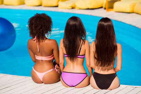 Diversity of ethnicity, colors and beauty of females. Back view of three hot ladies with healthy and nice hair, smooth, depilated, shining skin, perfect figures sitting near pool. Bodycare concept Foto de archivo