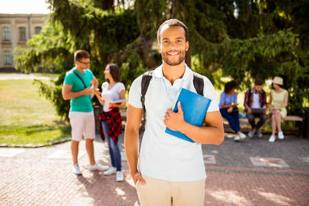 Young cheerful mulatto male nerdy student is standing with a notebook and hand in the pocket, his classmates are on the background, in a park near university