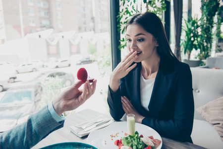 すぐに正式な摩耗で幸せな興奮してかなりブルネットの女性の彼女はショックを受けて、彼らは一緒に昼食を食べている間、彼氏は結婚の提案になって 写真素材 - 86614259