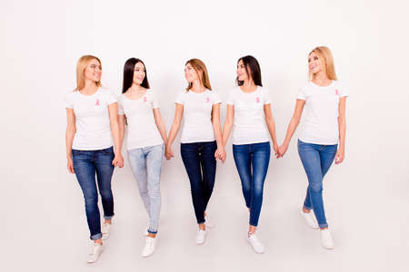 Life after fighting breast cancer exist. Carefree, happy, helthy, cured, cheerful five girls are holding each others arms, walking to new life together, with pink ribbons symbols on chest, world day Stock Photo