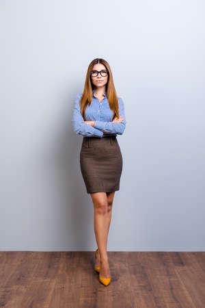 Groot formaat foto van elegante zakelijke dame advocaat in strikte outfit en bril, staande in flirterige pose met gekruiste handen en benen. Ze ziet er zo sexy en verleidelijk uit Stockfoto