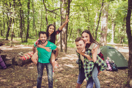 Close up of a four cheerful funky friends tourists. Camp in the sunny wood, tent and backpacks. Two guys are piggybacking their girlfriends, happy, smiling Stok Fotoğraf