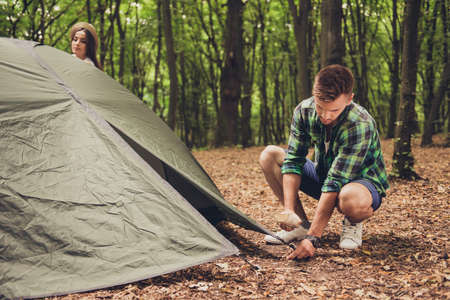 Close up of a young blond male tourist setting up a green tent in forest, on a fallen brown leaves, in a casual comfortable wear, green trees behind Banco de Imagens