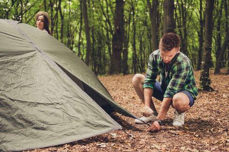 Sluit omhoog van een jonge blonde mannelijke toeristenvestiging een groene tent in bos, op gevallen gevallen bladeren, in een toevallige comfortabele slijtage, groene bomen erachter Stockfoto