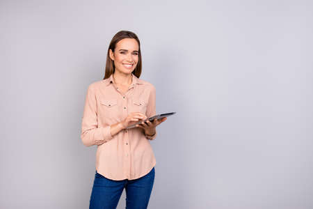 Successful young brunette entrepreneur in a beige shirt, jeans, is standing on the pure grey background with tablet, smiling, looking at the camera