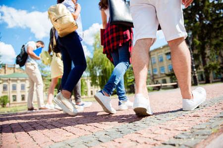 Low angle rear view shot of six student`s feet, they are walking outside in the park near te college building, sunny summer day, friends are enjoying their company
