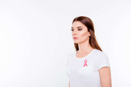 Women breast cancer, medicine, survival, femenine power concept - young brunette woman in white t shirt with pink breast cancer awareness ribbon on her chest, isolated on white background