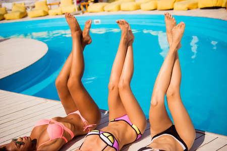 Women body care, pedicure, epilation, beauty, health concept. Close up cropped shot of long female legs of three multi ethnic hot chics with perfect smooth soft skin, getting tanned at beach