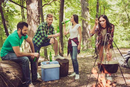 Chillen bij het vuur in een kamp in zonnig bos. Het donkerbruine meisje controleert de maaltijd in vee, vrienden hebben bier Stockfoto
