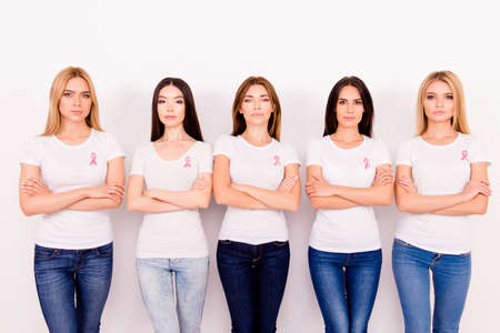 Women power, strength, We are fighters, we can do it together! Concept of ladies breast cancer danger, cure, hope and friendship, support. Five young girls with crssed arms, pink ribbons on chests