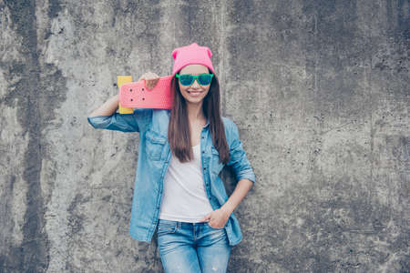 Be a star! Young attractive hipster girl with skate board on concrete wall`s background, in denim outfit, pink hat and green eyewear, holds a long board