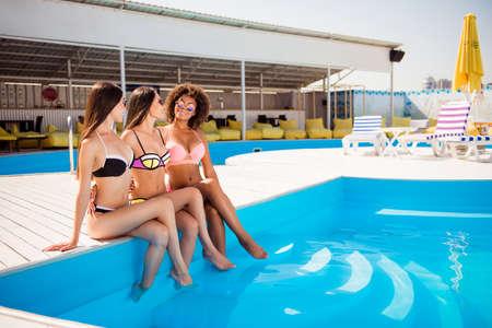Drie hete dames, poseren in zwemkleding en -brillen, knuffelen, zittend op witte houten vloer bij het zwembad met helder blauw water, geweldige vakantie samen op een chique toeristenoord