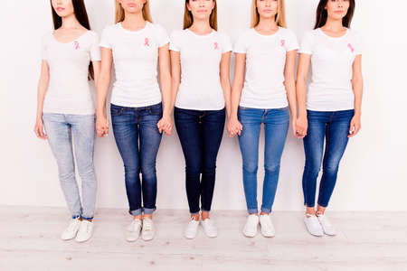 Women unity, connection, oneness, trust, love, help, support, breast cancer. Cropped shot of five ladies, holding arms of each other, with pink ribbon symbols on their chests, in jeans and gum shoes Stock Photo