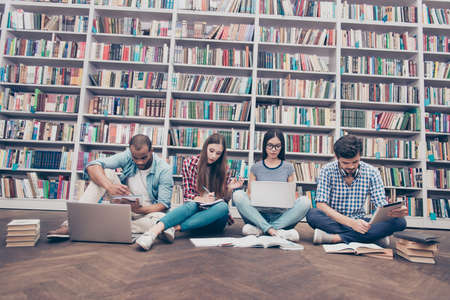 Tiro de ángulo bajo de cuatro estudiantes internacionales inteligentes ratón de biblioteca en el estudio de la biblioteca, sentado con las piernas cruzadas en el piso, usando libros y dispositivos, fondo de estanterías de libros enormes