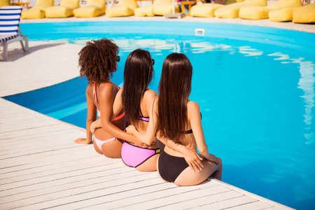 Back view of three hot skinny brunette ladies with healthy and nice hair, smooth, depilated, shining skin, idyllic figures sitting near pool on white wooden floor, cuddling, holding waists Banco de Imagens - 87388933