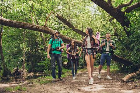 Trekking, kamperen en het concept van het wilde leven. Twee stellen vrienden lopen in het zonnige voorjaarsbos, praten en lachen, allemaal opgewonden en angstig, junglepaden Stockfoto