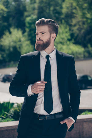 Vertical portrait of confident young red bearded stylish businessman in a costly suit holding hand in pocket and waiting for his business colleague outdoors