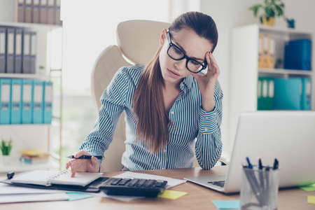 Close up of ponder young business lady accountant in formal wear and with pony tale, glasses, sitting at her work place and counting costs and expenses