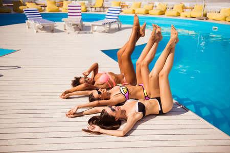 Vrouwen lichaamsverzorging, pedicure, epileren, schoonheid, gezondheid, huidbeschermingsconcept. Vrouwelijke benen van drie vriendinnen met een perfecte gladde, zachte huid, gebruind bij het zwembad op vakantie feestje Stockfoto - 87388936