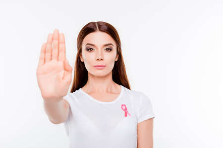 Say stop to breast cancer! Young brunette woman is making stop gesture with palm of her hand, standing in white outfit, on a white background, serious