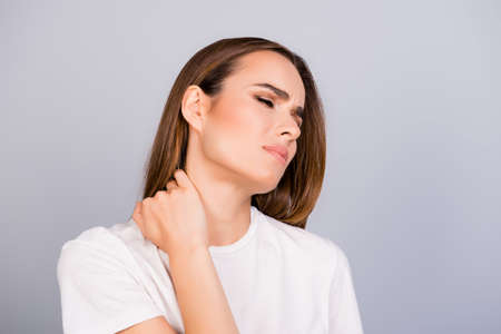 Young frustrated brown haired lady is having a strong pain in neck. She is in a white tshirt, massaging the neck, with pain grimace Stock Photo