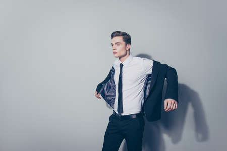 Young handsome guy with perfect hairstyle in suit wearing his jacket against gray background Stock Photo