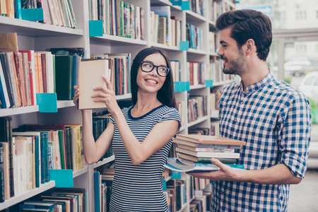 Couple of international students are in the library together after studies, smiling, dressed in comfortsble casual wear, holding books, helping each other. Book shelves background
